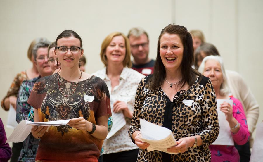 Two female members of Scottish Opera's Community Choir holding sheet music and smiling