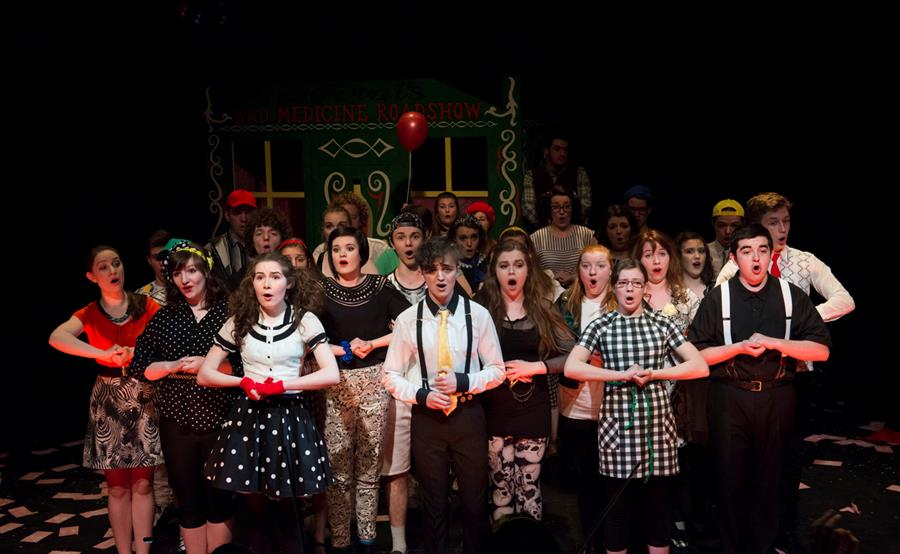 Scottish Opera's Connect Chorus standing with their hands clasped in a performance of Dr Ferret's Bad Medicine Roadshow