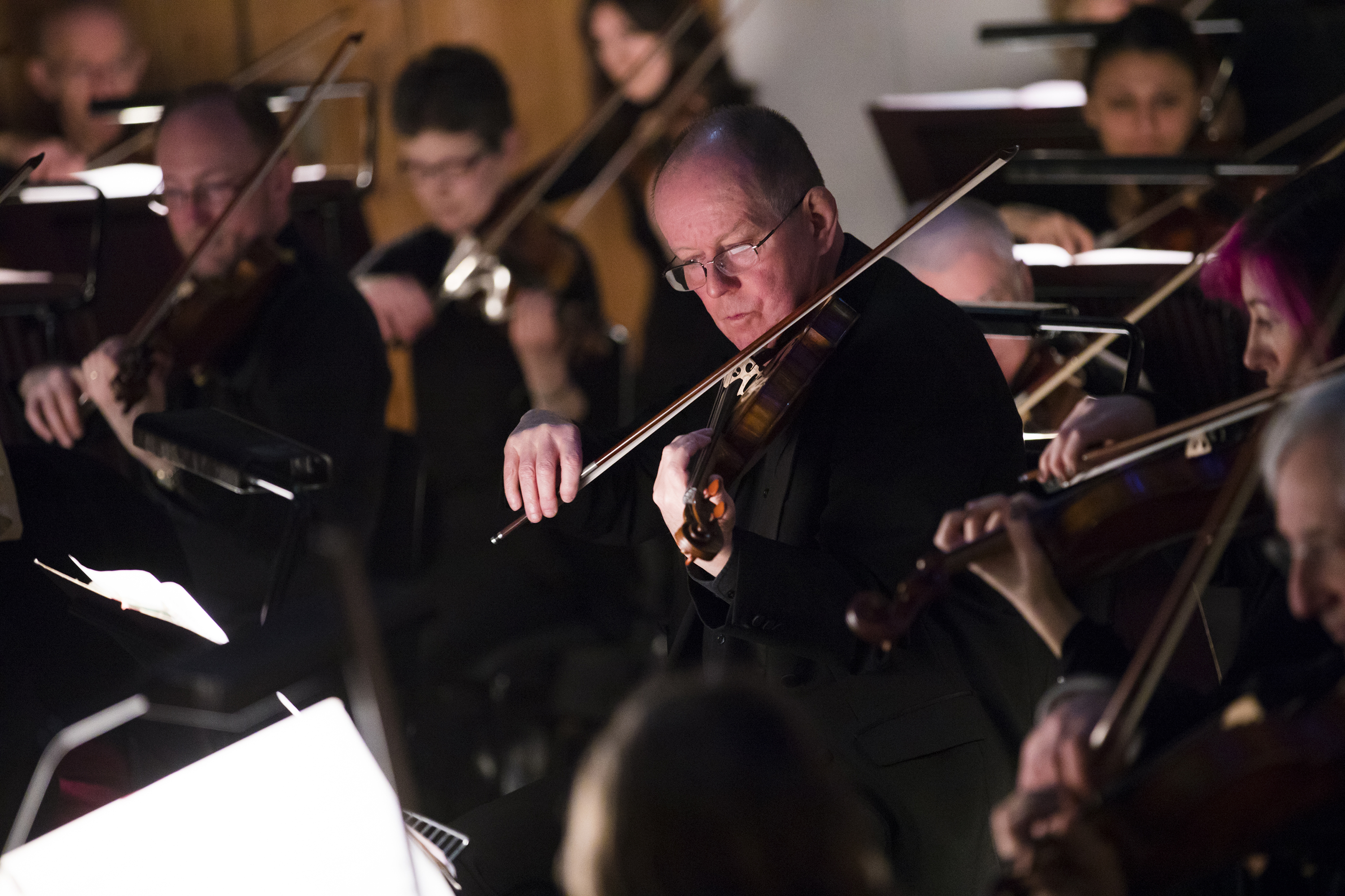 A man playing in the violin section of the orchestra